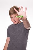 Boy holding fidget spinner. Young teenage boy holding fidget spinner in front of his face Stock Images