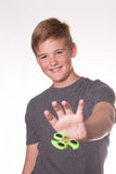 Boy holding fidget spinner. Young teenage boy holding fidget spinner in front of his face Stock Photos