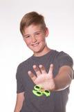 Boy holding fidget spinner. Young teenage boy holding fidget spinner in front of his face stock photos