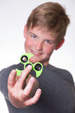 Boy holding fidget spinner. Young teenage boy holding fidget spinner in front of his face Stock Image