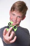 Boy holding fidget spinner. Young teenage boy holding fidget spinner in front of his face stock image