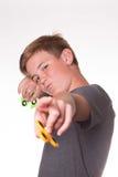 Boy holding fidget spinner. Young teenage boy holding fidget spinners pointing at camera Royalty Free Stock Photo