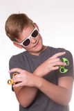 Boy holding fidget spinner. Young teenage boy in sunglasses holding fidget spinners and crossing his arms stock images