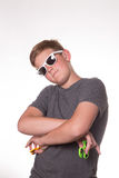 Boy holding fidget spinner. Young teenage boy in sunglasses holding fidget spinners and crossing his arms royalty free stock photos