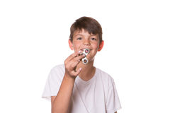 Boy holding fidget spinner. Younger boy holding fidget spinner in front of his face Stock Images