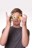 Boy holding fidget spinners in front of eyes. Young teenage boy iholding fidget spinners in front of his face stock photo