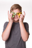 Boy holding fidget spinners in front of eyes. Young teenage boy iholding fidget spinners in front of his face royalty free stock photo