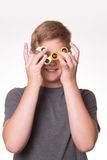Boy holding fidget spinners in front of eyes. Young teenage boy iholding fidget spinners in front of his face Stock Images