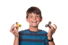 Boy holding fidget spinners in front of eyes. Younger boy holding fidget spinners in each hand Stock Photo