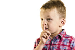 Boy holding a finger near lips Royalty Free Stock Images