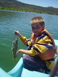 Boy holding fish. Boy holding the catch of the day sitting in our rented paddle boat Royalty Free Stock Photos