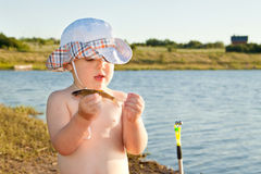 Boy holding a fish. Boy (small fisherman) stands on the bank of the pond, holding a fish and looks at her Royalty Free Stock Photography