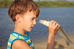 Boy holding fish and smiling Royalty Free Stock Photos