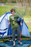 Boy Holding Fishing Net And Rod Against Tent. Full length portrait of preadolescent boy holding fishing net and rod against tent Stock Photo