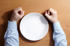 Boy holding a fists sitting at the table with white empty plate. Royalty Free Stock Photos