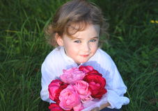 Boy holding flowers. Smiling boy holding a  bunch of roses in the garden Royalty Free Stock Image