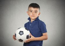 Boy holding football ball. Future soccer player. Boy holding football ball isolated grey wall background. Confident face expression Royalty Free Stock Photos