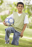 Boy holding football in park Royalty Free Stock Photos