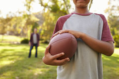 Boy holding football in park, crop, dad in background Stock Photos