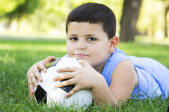 Boy holding football in park. Boy outdoors lying on green grass with soccer ball under his head Stock Photography
