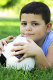 Boy holding football in park. Boy outdoors lying on green grass with soccer ball under his head Stock Photo