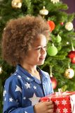 Boy Holding Gift In Front Of Christmas Tree Royalty Free Stock Photography