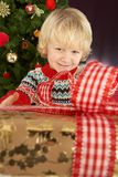Boy Holding Gift In Front Of Christmas Tree Stock Photography