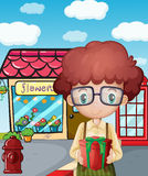 A boy holding a gift in front of the flower shop Stock Photo