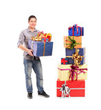 Boy holding a gift next to a pile of gifts Royalty Free Stock Photography