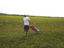Children spinning on the green grass in the field. Boy holding a girl for her hands and spinning her on the green grass in the field Stock Photos