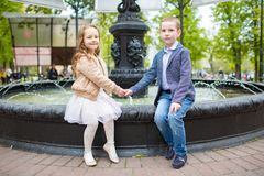 Boy holding girl`s hand. Children sitting at the fountain outdoor. Love friendship fun concept. Small adults stock image