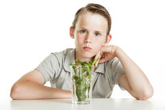 Boy holding glass with herbs on white background Royalty Free Stock Photo