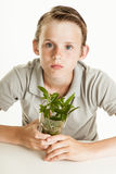 Boy holding glass with weeds on white background Royalty Free Stock Photos