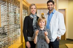 Boy Holding Glasses With Mother And Optician In Royalty Free Stock Photos