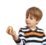 Boy holding a golden egg Stock Photos