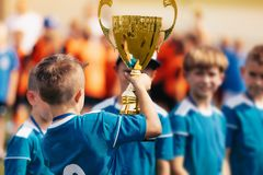 Boy holding golden trophy and celebrating sport success with team. Champions of school sports tournament stock photo