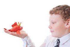 Boy holding a goldfish out of plasticine. Figure goldfish made of plasticine Royalty Free Stock Images