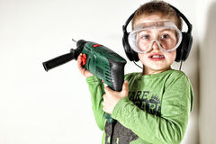 Boy holding green drilling machine on his shoulder Stock Photos
