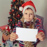 Boy holding greeting card. Christmastime Stock Photo