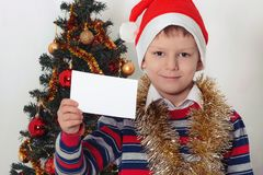 Boy holding greeting card. Christmastime Royalty Free Stock Photo