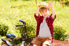 Boy holding hamburger above his head in park Stock Photography