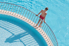 Boy holding the handrail and is going to dive. Into the pool stock image