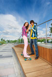 Boy holding hands of girl on skateboard Royalty Free Stock Photography