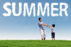 Boy holding hands with his father at field. Cheerful little boy playing on the field while holding hands with his father under a summer's cloud Stock Images