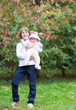 Boy holding his baby sister standing under a red tree Royalty Free Stock Images