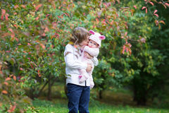 Boy holding his baby sister standing under a red tree Stock Image