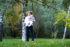 Boy holding his baby sister standing under a tree. Boy holding his baby sister standing under an autumn tree Royalty Free Stock Photography