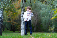 Boy holding his baby sister standing under a tree. Boy holding his baby sister standing under an autumn tree Royalty Free Stock Images