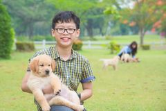 Boy holding his dog and smiles in park stock images