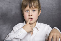 A boy holding his fingers in his mouth. A child on a gray background. The child is in focus, face and hands closeup. His face has a thoughtful look Royalty Free Stock Photography